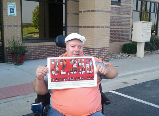 Photo: Brad holding up a sign 32, 250 total HCBS participants in Kansas