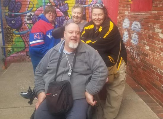Photo: SACK self advocates in front of a graffiti background
